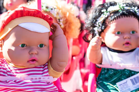 Colorful eyed baby with plastic hair sold outside in front of store for girls.