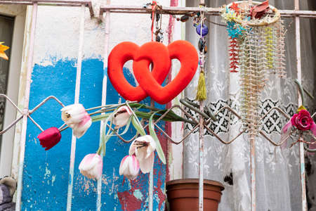 Iron bars of the old house. It has ornaments with red hearts and fake roses.