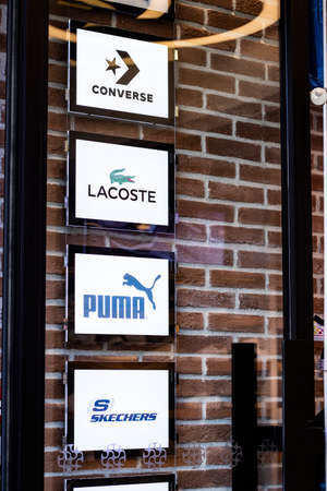 Puma, Converse, Lacoste, Skechers logos of the brands are hung behind the door.