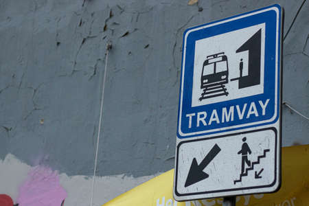 Blue signage indicating the tram station. Colorful wall in the back. Banco de Imagens
