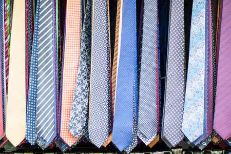 Krawaty w różnych wzorach i odmianach. Sfotografowany przed sklepem. Zbliżenie.