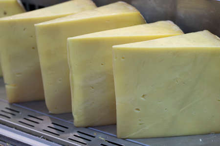 Close-up of cheddar cheese is sold in the market. Triangular slice shaped. It is produced in Turkey.