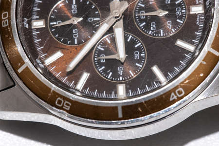 Close-up of a used wristwatch. The outer case is metallic and the inside is brown.