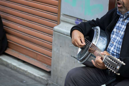 Close up of adult giving a concert with baglama on the street. She leaned her back against the wall. The photo was taken in Taksim.