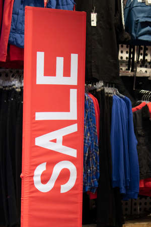 Sale text in white on a red table. In the back, the clothing store appears.