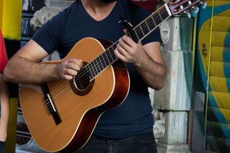 Close up of young giving a concert with guitar on the street. She leaned her back against the wall. The photo was taken in Taksim.