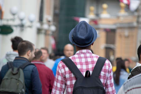 A teenager with a checkered shirt, a fedora and a backpack. The man is turned back and photographed outside. Stock fotó