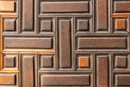 Old wooden door with geometric pattern. Wooden surface is tinted in warm color.