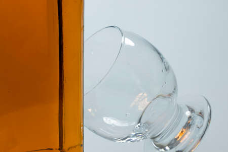 Whiskey bottle and cross-standing glass based on the bottle. The photo was taken on white background and in the studio. Foto de archivo