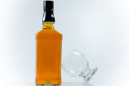 Whiskey bottle and cross-standing glass based on the bottle. The photo was taken on white background and in the studio. Banque d'images