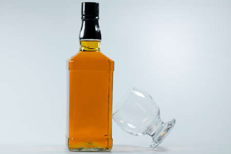 Whiskey bottle and cross-standing glass based on the bottle. The photo was taken on white background and in the studio.