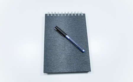 Concept of notepad phone pen. The photo was taken on white background and studio.