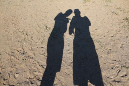 Shadow of two men on the sand at the beach. Turkey