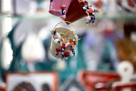 Colorful decorations made of evil eye beads in a small bucket. Close-up.
