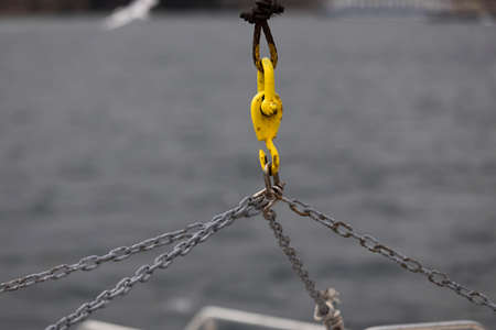 The metal chain is used for lifting weights. In the background the sea is blurred. Close-up.