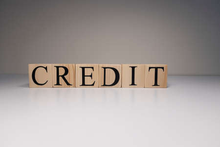 The word credit from wooden blocks. Business and banking concept. Spot light on white background.