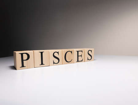 Pisces word on wooden cubes on white background. Photographed in the studio and in spot light. Zodiac or star signs consists of 12 horoscopes.
