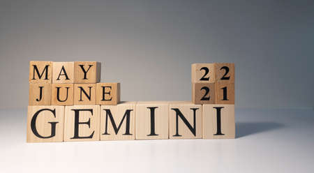 Gemini word on wooden cubes on white background. Photographed in the studio and in spot light. Zodiac or star signs consists of 12 horoscopes.