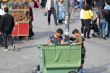 Istanbul, Turkey - October-27.2019: Children looking for food in a trash can. People are around.