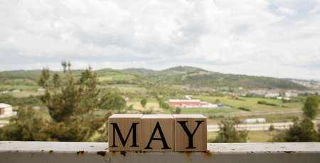 The word may from wooden cubes. Spring concept. Cloudy sky and mountains in the background.