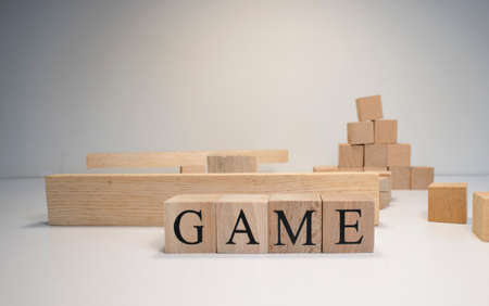 game word made of wooden cubes. Construction from cubes in the background. Child and entertainment concept.