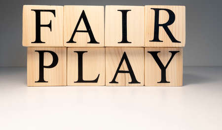 Fair play word from wooden cubes. Spotlight and white background. Sports competitions and law.