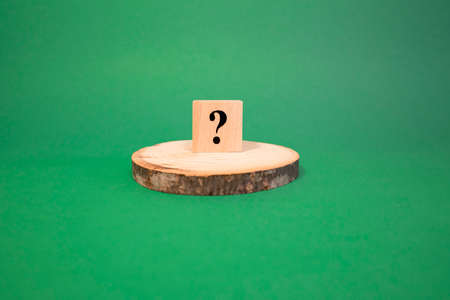 The word question mark made of wooden cubes. The background is green and photographed in the studio Reklamní fotografie - 150732360
