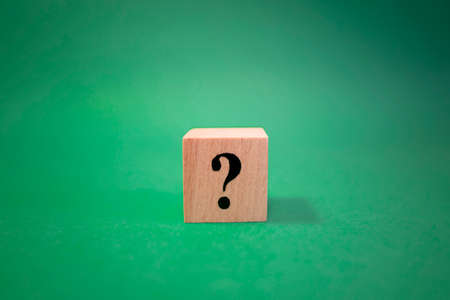 The word question mark made of wooden cubes. The background is green and photographed in the studio
