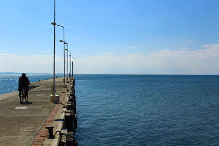 Seaside and concrete pier. Traditionally dressed man riding a bike on the pier.