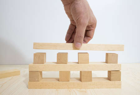 Building from wooden cubes and rods. The photo was taken on the white background and on the table.