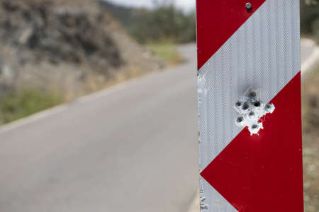 Red road stop sign full of bullet holes Stok Fotoğraf