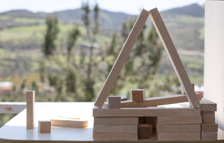 Building from wooden cubes and rods. A photo was taken on the table. Forest mountain landscape in the background.