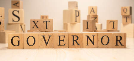 The word governor is from wooden cubes. Economy state government terms. Background made of wooden letters.