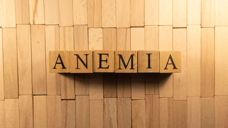 The word anemia was created from wooden letter cubes. Illness and health. close up.