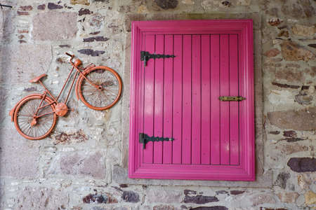 Pink wooden window and decorative orange bicycle on a stone wall, decorative object