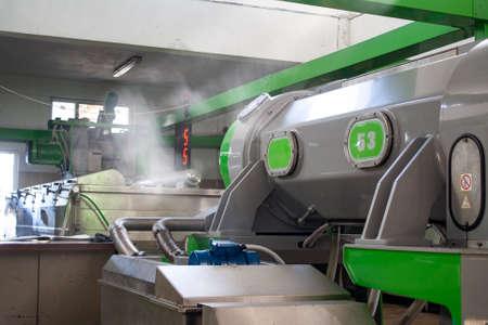 Gewinnung von Öl aus Oliven in einer modernen Fabrik. Olivenölmaschine in der Fabrik. Standard-Bild