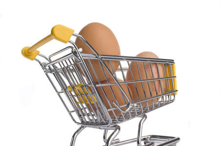 shoppingcart: brown eggs in shopping-cart. The cart is a model, different scale of eggs and cart. Stock Photo