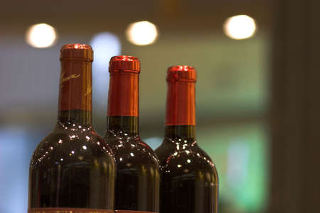 closed corks: three bottles of red wine at a bar. blurring background