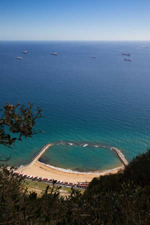 Gibraltar, looking East from the Upper Rock to the beach sandy bay,  tankers lying in front of the coast,