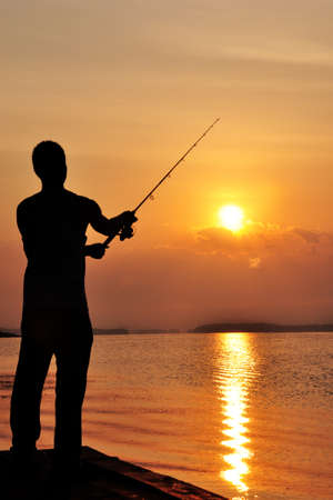 Silhouette of man fishing off the dock at sunset