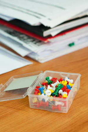 Colorful thumbtacks pinned and documents on office desk photo