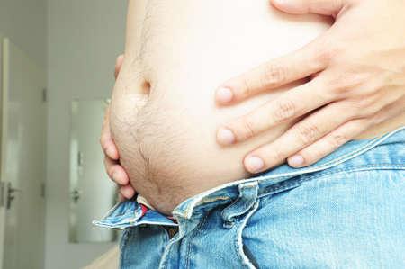 ombligo: Hombre gordo con una gran barriga no puede vistiendo jeans Foto de archivo