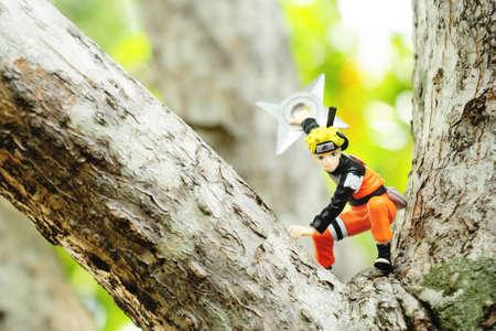 realism: BANGKOK - DECEMBER 07, 2014 : A realism concept, A figure of Uzumaki Naruto in action throwing shuriken on the big tree on December 07, 2014 at Phuttabucha, Bangkok, Thailand. Editorial
