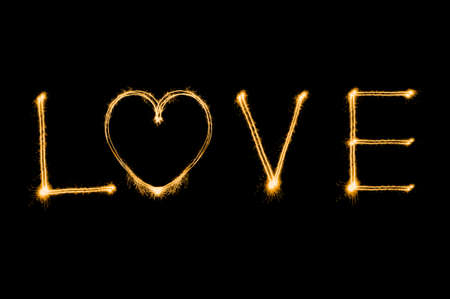 valentines: Love writing by sparkler firework isolated on black background for Valentines day