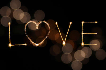 Love writing by sparkler firework on gold defocused bokeh background for Valentines day photo