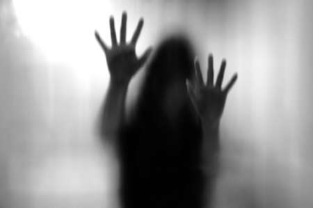 Horror woman behind the matte glass in black and white. Blurry hand and body figure abstraction.