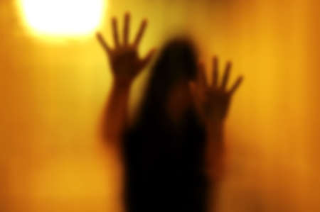 haunted: Woman behind the matte glass. Blurry hand and body figure abstraction.