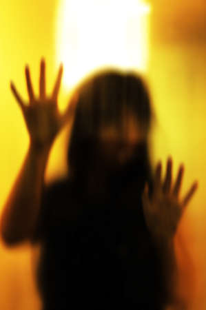abducted: Horror woman behind the matte glass. Blurry hand and body figure abstraction.