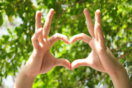 handsign: Female hands in the form of heart isolated on green background