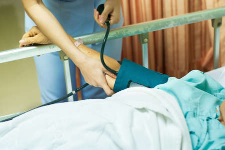 bp: Nurse and patient. Measurement of blood pressure in a hospital